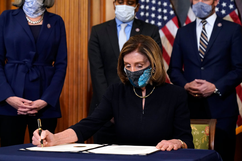 House Speaker Nancy Pelosi of Calif., signs the articles of impeachment against President Donald Trump in an engrossment ceremony before transmission to the Senate for trial on Capitol Hill, in Washington, Wednesday, Jan. 13, 2021. (AP Photo/Alex Brandon)
