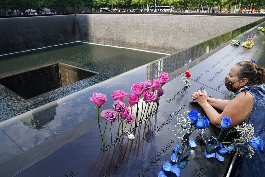 FILE - In this Friday Sept. 11, 2020, file photo, a mourner prays over the etched name of the deceased Emilio Pete Ortiz at the National September 11 Memorial and Museum in New York. Authorities say a U.S. Army soldier has been arrested in Georgia on terrorism charges after he spoke online about plotting to blow up the 9/11 Memorial in New York City and attack U.S. soldiers in the Middle East. (AP Photo/John Minchillo, File)