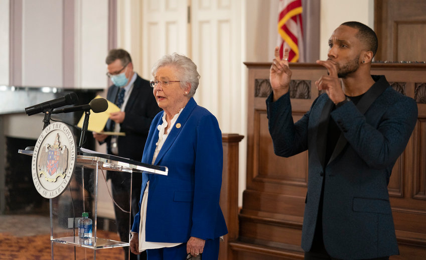 Gov. Kay Ivey speaks at a press conference in Montgomery Thursday with state health officer Scott Harris (behind her), as the state emergency orders on COVID-19 were extended  until March 5. A sign language interpreter also signed her remarks.