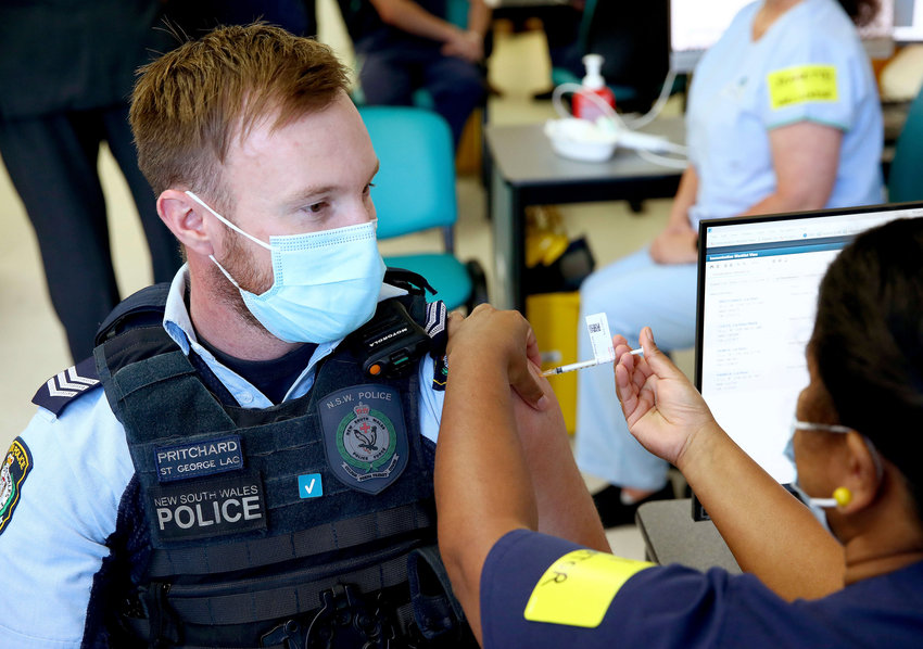 New South Wales Police officer Lachlan Pritchard receives the Pfizer vaccine at the Royal Prince Alfred Hospital Vaccination Hub in Sydney, Australia, Monday, Feb. 22, 2021.Australia has started its COVID-19 vaccination program days after its neighbor New Zealand with both governments deciding their pandemic experiences did not require regulation short cuts. (Toby Zerna/Pool via AP)