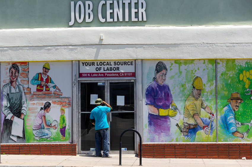 FILE - In this May 7, 2020 file photo, a person looks inside the closed doors of the Pasadena Community Job Center in Pasadena, Calif., during the coronavirus outbreak. A state report released Tuesday, March 2, 2021, details the pandemic's toll on California workers and shines light on who was most affected by job losses and layoffs.  (AP Photo/Damian Dovarganes, File)