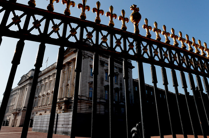 Buckingham Palace is seen behind a fence in London, Tuesday, March 9, 2021. Britain's royal family is absorbing the tremors from a sensational television interview by Prince Harry and the Duchess of Sussex, in which the couple said they encountered racist attitudes and a lack of support that drove Meghan to thoughts of suicide. (AP Photo/Frank Augstein)