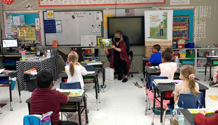 """State Rep. Connie Rowe reads """"Lucy Meets A Logger"""" to a group of students at T.R. Simmons Elementary School."""