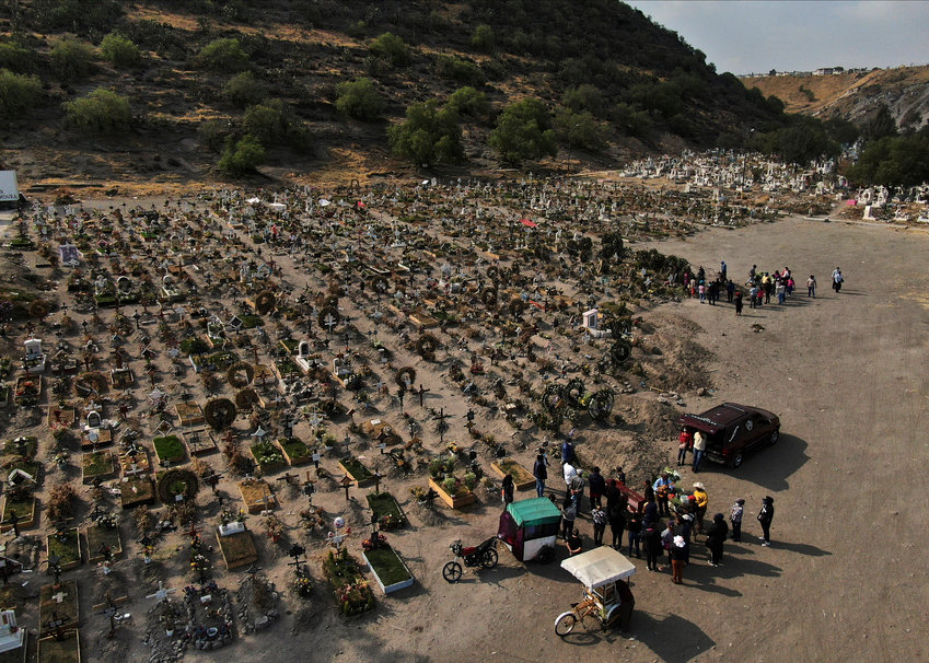 FILE - In this March 17, 2021 file photo, family members attend the burial service of a relative who died from COVID-19 in the Chalco cemetery just outside Mexico City, amid the new coronavirus pandemic. (AP Photo/Fernando Llano, File)