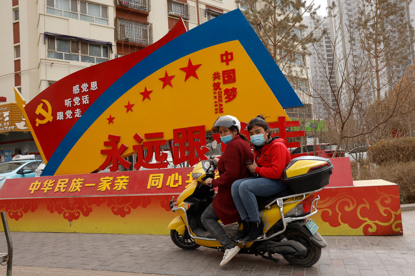 """Residents wearing masks past by a Chinese government propaganda with slogans some of which reads """"Forever follow the Party"""" and """"China's Ethnicities One Family"""" in the city of Aksu in western China's Xinjiang region on Thursday, March 18, 2021. China on Friday announced sanctions on British individuals and entities following the U.K.'s joining the EU and others in sanctioning Chinese officials accused of human rights abuses in the Xinjiang region.  (AP Photo/Ng Han Guan)"""