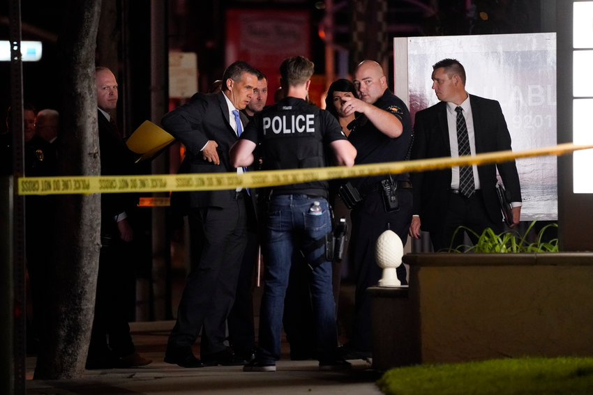 Investigators gather outside an office building where a shooting occurred in Orange, Calif., Wednesday, March 31, 2021. The shooting killed several people, including a child, and injured another person before police shot and wounded the suspect, police said. (AP Photo/Jae C. Hong)