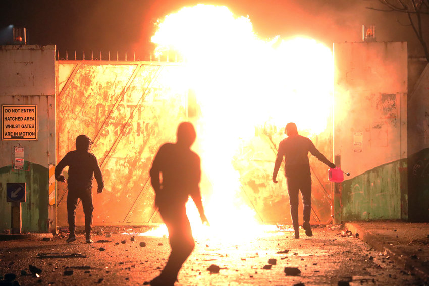 Nationalists and Loyalists clash with one another at the peace wall on Lanark Way in West Belfast, Northern Ireland, Wednesday, April 7, 2021. The police had to close roads into the near by Protestant area as crowds from each divide attacked each other. (AP Photo/Peter Morrison)