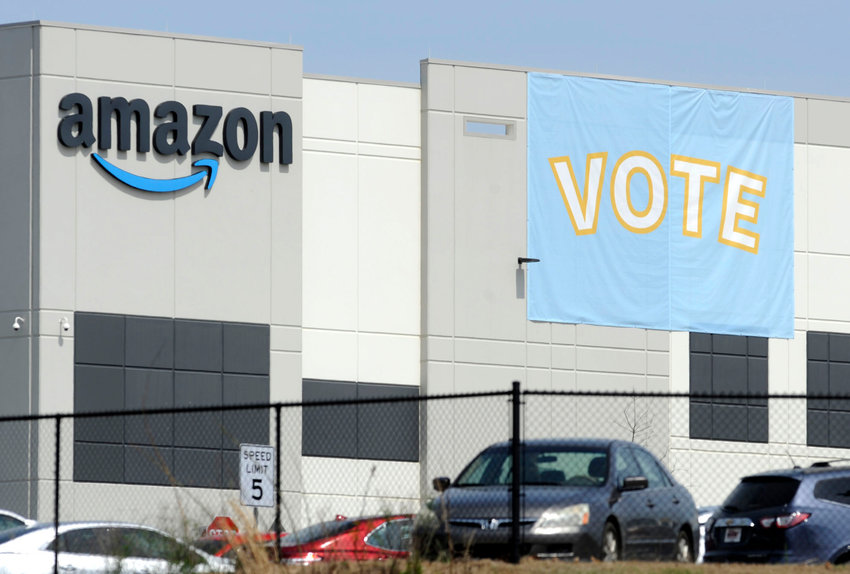 A banner encouraging workers to vote in labor balloting is shown at an Amazon warehouse in Bessemer, Ala., on Tuesday, March 30, 2021. Organizers are pushing for some 6,000 Amazon workers to join the Retail, Wholesale and Department Store Union on the promise it will lead to better working conditions, better pay and more respect. Amazon is pushing back, arguing that it already offers more than twice the minimum wage in Alabama and workers get such benefits as health care, vision and dental insurance without paying union dues. (AP Photo/Jay Reeves)