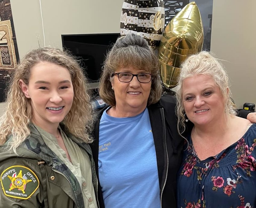 Joan Hall, center, celebrates her retirement with coworkers Megan Johnson and Rhonda Guthrie.