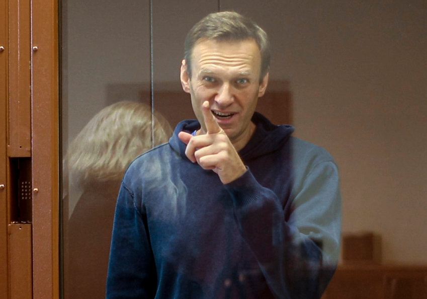 In this photo taken from a footage provided by the Babuskinsky District Court  Tuesday, Feb. 16, 2021, Russian opposition leader Alexei Navalny gestures as he stays a cage during a hearing on his charges for defamation in the Babuskinsky District Court in Moscow, Russia. Russian opposition leader Alexei Navalny attends a court hearing in Moscow ... Navalny is accused of defaming a World War II veteran who was featured in a video last year advertising constitutional amendments that allowed an extension of President Vladimir Putin's rule. (Babuskinsky District Court Press Service via AP)