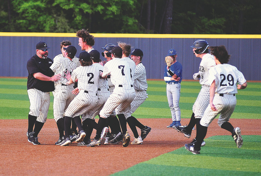 Jasper players mob Carson Alvis after his game-winning hit against Mortimer Jordan in Game 3 of their first-round series at Valley Park on Friday. The Vikings won the game 5-4, earning a spot in next week's second round.