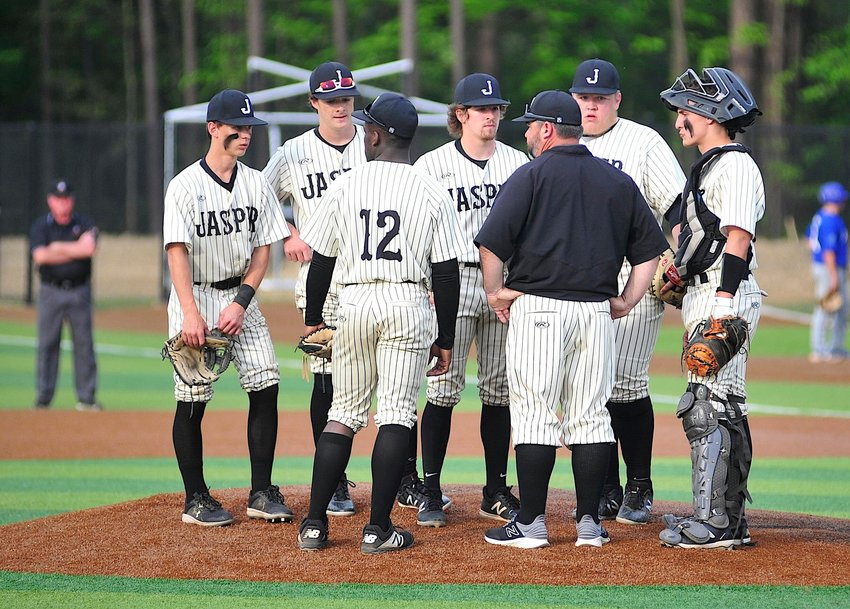 Jasper coach Pat Ware talks to players on the mound during the Vikings' first-round playoff series against Mortimer Jordan. Jasper hosts Oxford in the second round starting today.