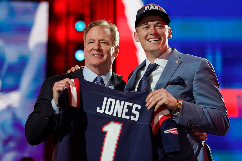 Alabama quarterback Mac Jones, right, holds a team jersey with NFL Commissioner Roger Goodell after the New England Patriots selected him with the 15th pick in the NFL football draft, Thursday April 29, 2021, in Cleveland. (AP Photo/Tony Dejak)