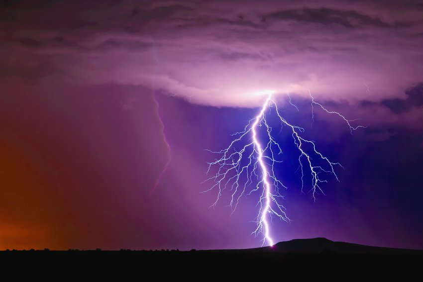 A single bolt of lightning striking the slope of the Arlington Mesa in Arlington Arizona during the 2015 Monsoon season. The bolt has a large number of branches making it look like a giant plant root made of light.