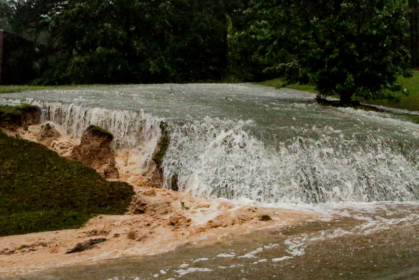 A hillside is eroded away as torrential rainfall falls Tuesday, May 4, 2021 in Vestavia, Ala. (AP Photo/Butch Dill)