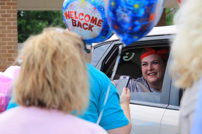 Amber Gilliland greets well-wishers at a homecoming celebration organized on Wednesday at Midway Church of Christ. Gilliland, a local teacher and mom of two, was hospitalized for 126 days with COVID-19.