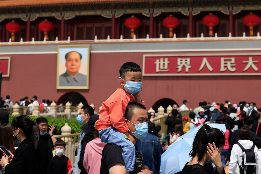 HOLD FOR STORY CHINA CENSUS  A man and child wearing masks visits Tiananmen Gate near the portrait of Mao Zedong in Beijing on Monday, May 3, 2021. (AP Photo/Ng Han Guan)