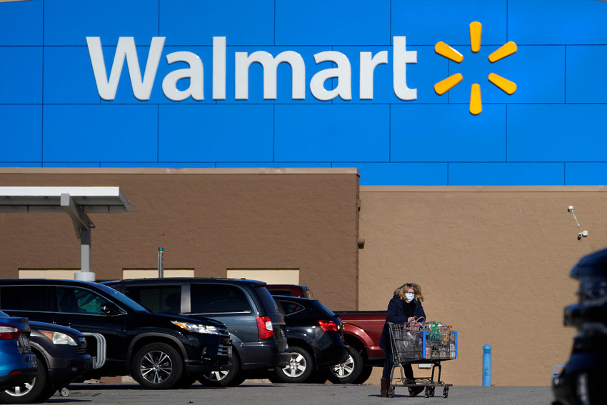 —HOLD FOR COURTNEY DITTMAR / DON KING—..A woman, wearing a protective mask due to the COVID-19 virus outbreak, wheels a cart with her purchases out of a Walmart store, Wednesday, Nov. 18, 2020, in Derry, N.H. (AP Photo/Charles Krupa)