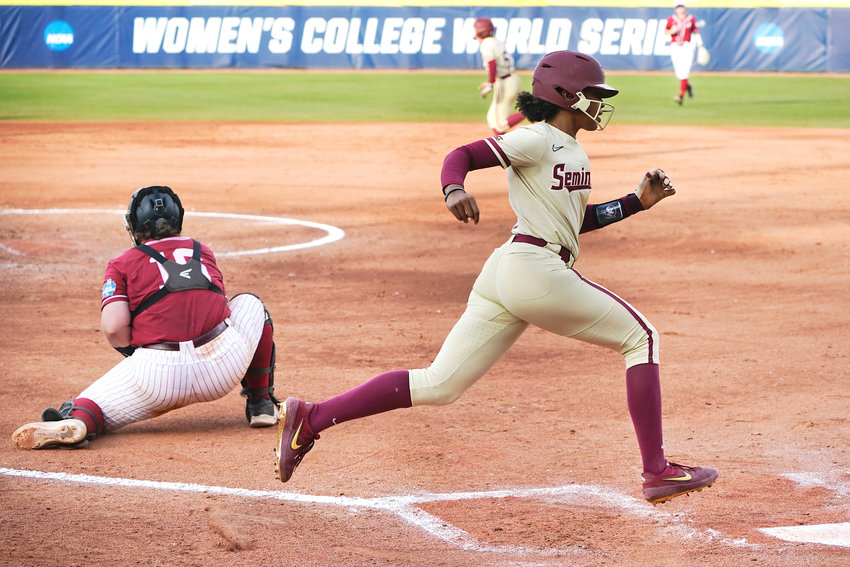 Florida State's Kalei Harding, right, scores behind Alabama catcher Bailey Hemphill, left, in the third inning of an NCAA Women's College World Series softball game Monday in Oklahoma City.