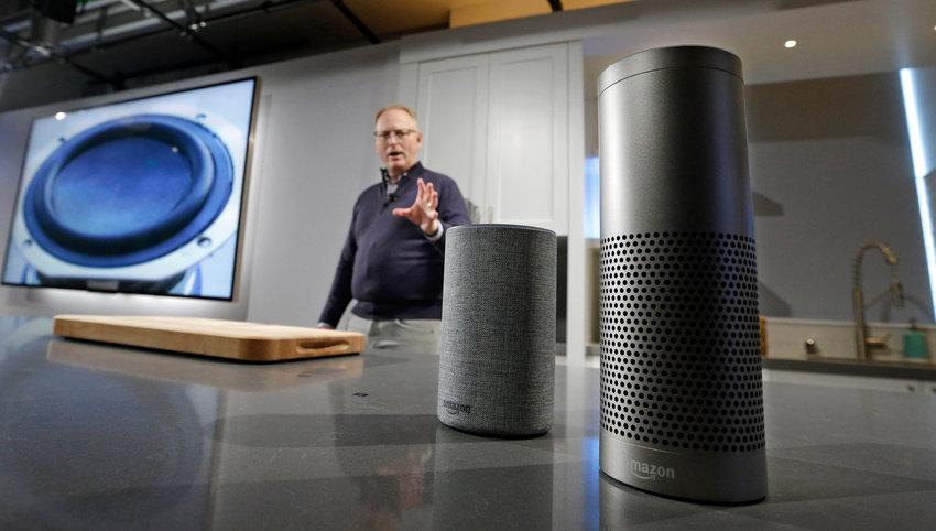 """David Limp, senior vice president of Devices and Services at Amazon, displays a new Echo, left, and a Echo Plus during an event announcing several new Amazon products by the company, Wednesday, Sept. 27, 2017, in Seattle. Amazon says it is cutting the price of its Echo smart speaker to $100 from $180, improving the sound quality and upgrading its appearance with six new """"shells."""" The online retailer also announced a premium version of the Echo Plus, which has improved sound and can act as the hub of a smart home and sell for $150. (AP Photo/Elaine Thompson)"""