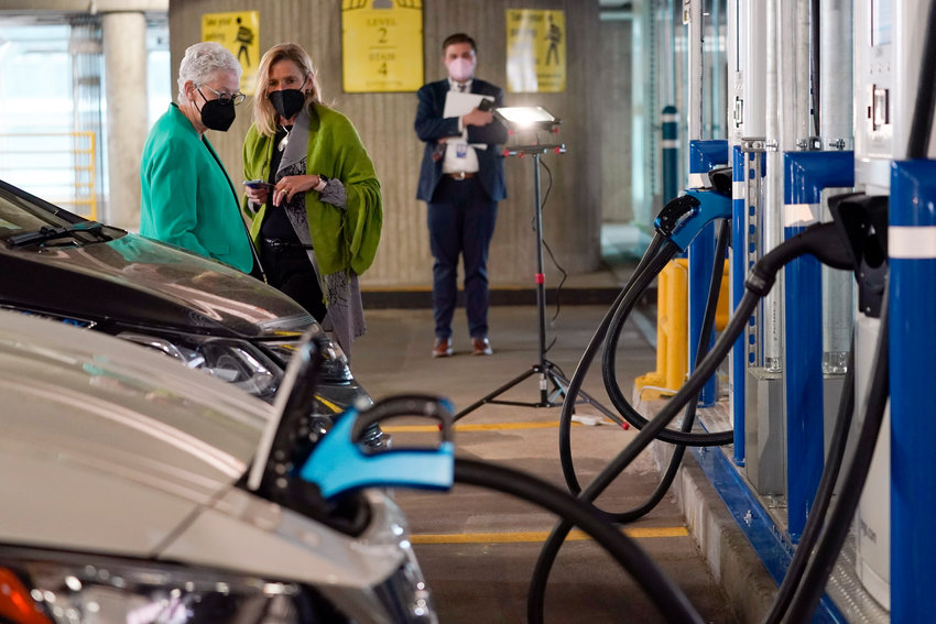 White House Climate Advisor Gina McCarthy, left, talks with EVgo Chief Executive Officer Cathy Zoi, before the start of an event near an EVgo electric car charging station at Union Station in Washington, Thursday, April 22, 2021. (AP Photo/Susan Walsh)