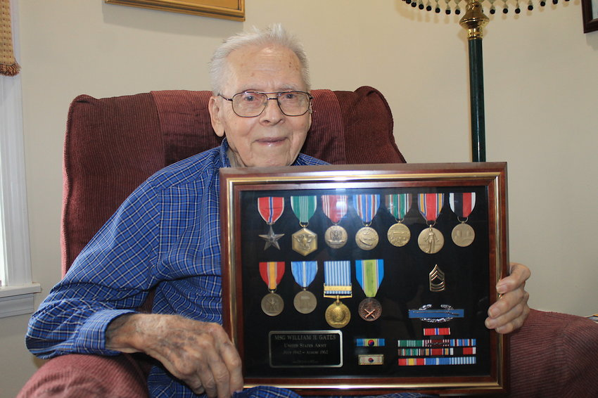 Herbert Gates holds a shadowbox displaying the medals he received during his military service.