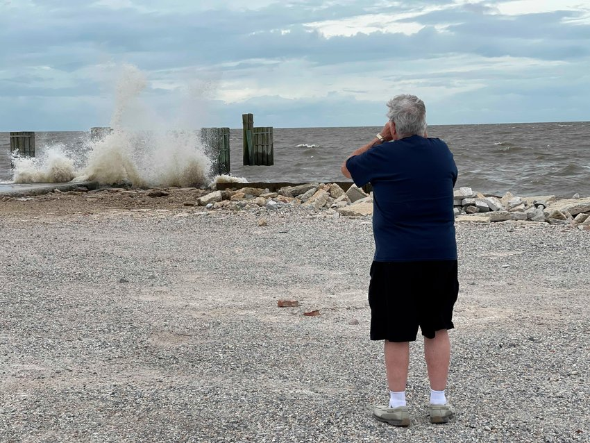 A man takes a photo of waves crashing into what once was a dock for a ferry that transported people from Bay St. Louis to Pass Christian, Miss., as a tropical system moves toward the Mississippi Coast on Friday, June 18, 2021.  Forecasters predict a tropical system will bring heavy rain, storm surge and coastal flooding to the U.S. Gulf Coast. The poorly organized disturbance was located Friday morning about 255 miles south of Morgan City, Louisiana.  (Justin Mitchell/The Sun Herald via AP)