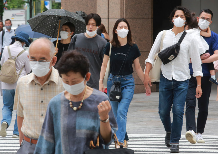 People wearing face masks to protect against the spread of the coronavirus walk on the street in Tokyo Tuesday, July 27, 2021 in Tokyo, (AP Photo/Koji Sasahara)
