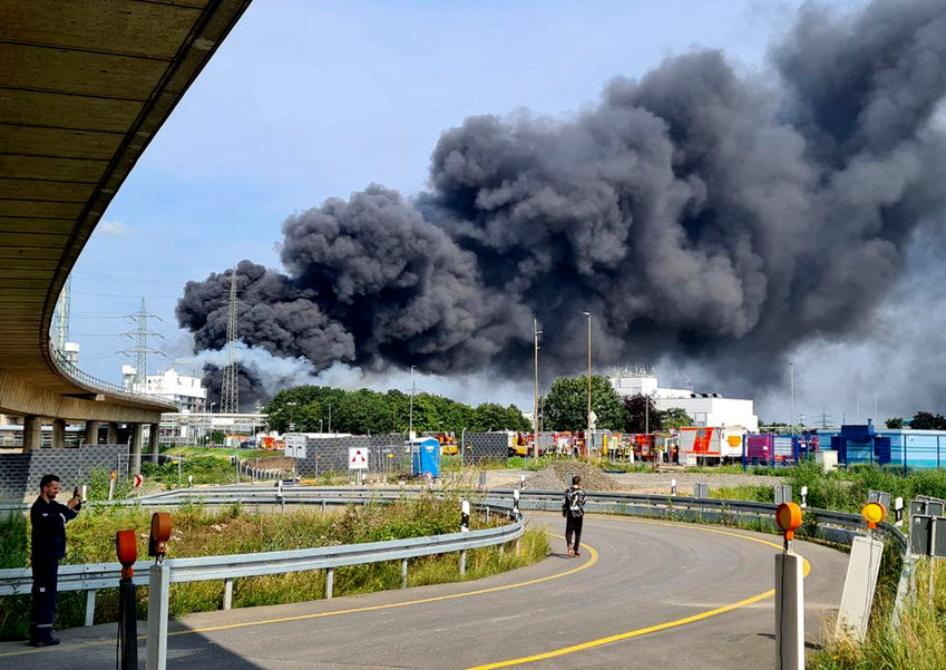 27 July 2021, North Rhine-Westphalia, Leverkusen: A dark cloud of smoke rises above the chemical park. Firefighters from the site fire department are on duty. Photo: Mirko Wolf/dpa
