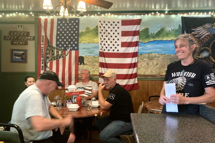 Pauline Bauer, right, speaks with customers from left, Ron Stevenson, 68, of Jamestown, N.Y., his cousin Glenn Robinson, 68, of Kane, Pa., and his half-brother Paul Boedecker, 71, of Warren, Pa., at Bauer's restaurant, Bob's Trading Post, Wednesday,  July 21, 2021, in Hamilton, Pa. Bauer is one of more than 540 people charged with federal crimes stemming from the Jan. 6 riot at the U.S. Capitol.  (AP Photo/Michael Kunzelman)