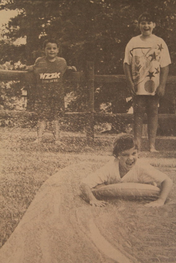 Shelley Allred, then 8, of Boldo, beats the heat by going down a Slip n' Slide while siblings Caleb and Emily watch in July 1993.