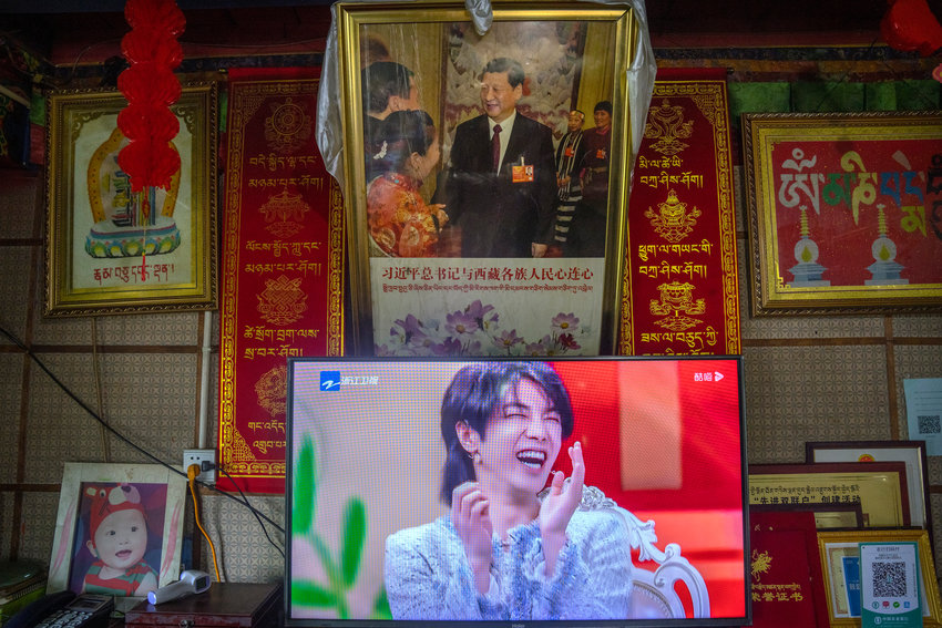 """FILE - In this June 4, 2021 file photo, a television shows a broadcast of a Chinese talk show program as it sits beneath a photo of Chinese President Xi Jinping in a home converted into a tourist homestay in Zhaxigang village near Nyingchi in western China's Tibet Autonomous Region. China's government banned effeminate men on TV and told broadcasters Thursday to promote """"revolutionary culture,"""" broadening a campaign to tighten control over business and society and enforce official morality. (AP Photo/Mark Schiefelbein, File)"""