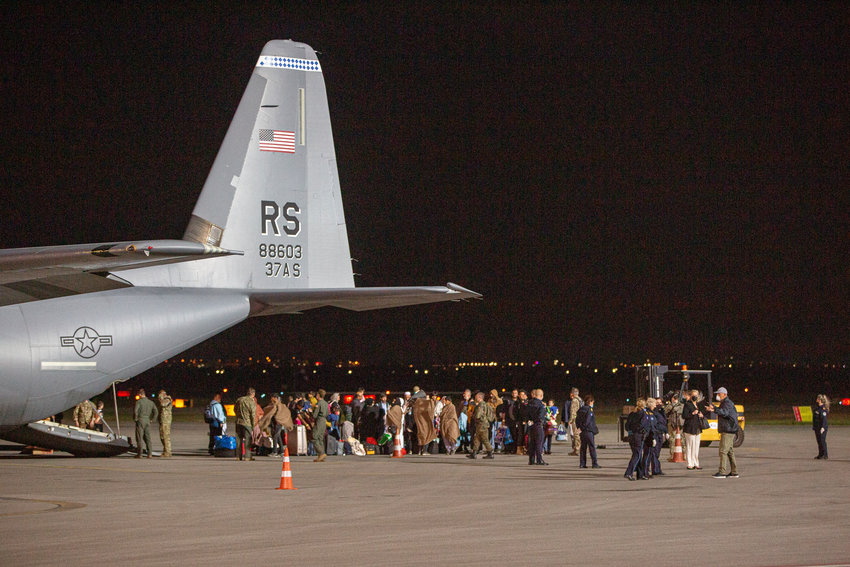 FILE - In this Aug. 29, 2021, file photo families evacuated from Kabul, Afghanistan, walk past a U.S Air Force plane that they arrived on at Kosovo's capital Pristina International Airport. The Afghans came from the Ramstein military base in Germany, and they will be housed near the U.S. military Camp Bondsteel, 40 kilometers (25 miles) south of the capital Pristina. (AP Photo/Visar Kryeziu, File)