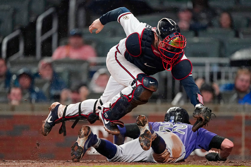 Colorado Rockies Sam Hilliard (22) slides under Atlanta Braves catcher Travis d'Arnaud (16) to score on a bunt by Antonio Senzatela during the fifth inning of a baseball game Wednesday, Sept. 15, 2021, in Atlanta. (AP Photo/John Bazemore)