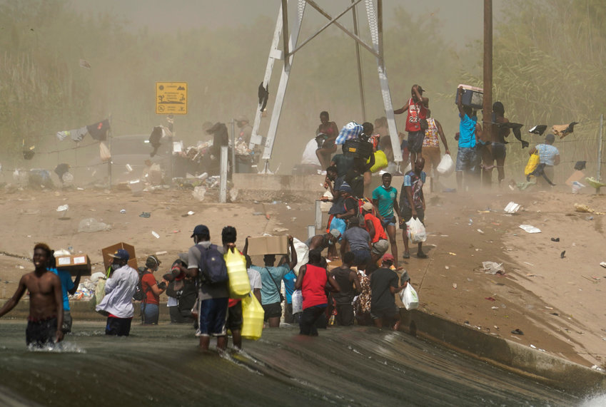 A dust storm moves across the area as Haitian migrants use a dam to cross into and from the United States from Mexico, Saturday, Sept. 18, 2021, in Del Rio, Texas. The Biden administration plans the widescale expulsion of Haitian migrants from a small Texas border city by putting them on on flights to Haiti starting Sunday, an official said Friday, representing a swift and dramatic response to thousands who suddenly crossed the border from Mexico and gathered under and around a bridge.(AP Photo/Eric Gay)