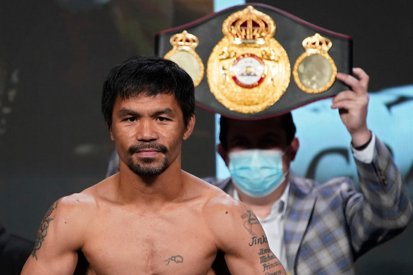 Manny Pacquiao, of the Philippines, poses for photographers during a weigh-in Friday, Aug. 20, 2021, in Las Vegas. Pacquiao is scheduled to fight Yordenis Ugas, of Cuba, in a welterweight championship bout Saturday in Las Vegas. (AP Photo/John Locher)