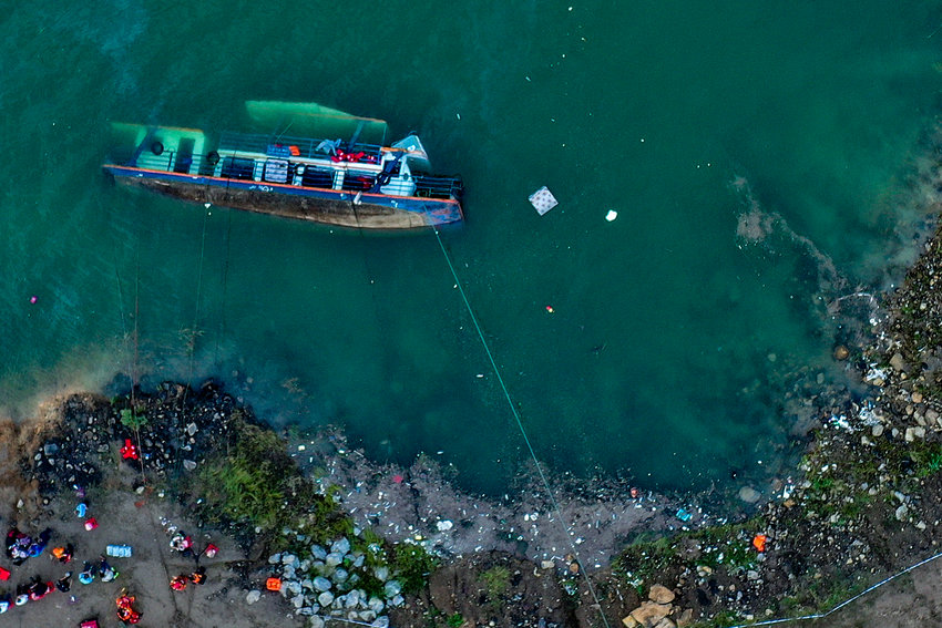 In this photo released by Xinhua News Agency, rescuers work at the site where a passenger ship overturned in Liupanshui in southwest China's Guizhou province, Sunday, Sept. 19, 2021. Several people were killed, with another five still missing after a ship capsized in a river in southwest China's Guizhou Province, according to state broadcaster CCTV. (Ou Dongqu/Xinhua via AP)