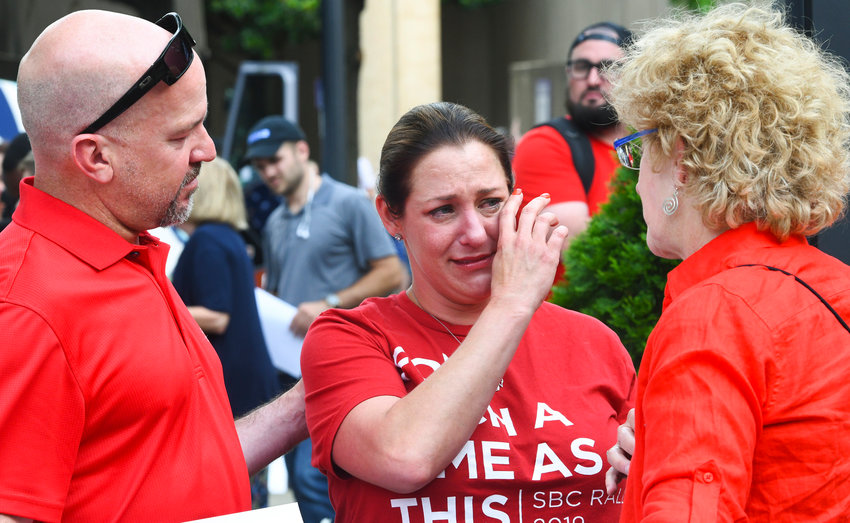 Sexual abuse victim Jules Woodson, center, of Colorado Springs, Colo., is comforted by her boyfriend Ben Smith, left, and Christa Brown while demonstrating outside the Southern Baptist Convention's annual meeting Tuesday, June 11, 2019, in Birmingham, Ala. The For Such A Time As This protest calls for a change in the way the SBC views and treats women and demands action to combat sexual abuse within the establishment. (AP Photo/Julie Bennett)