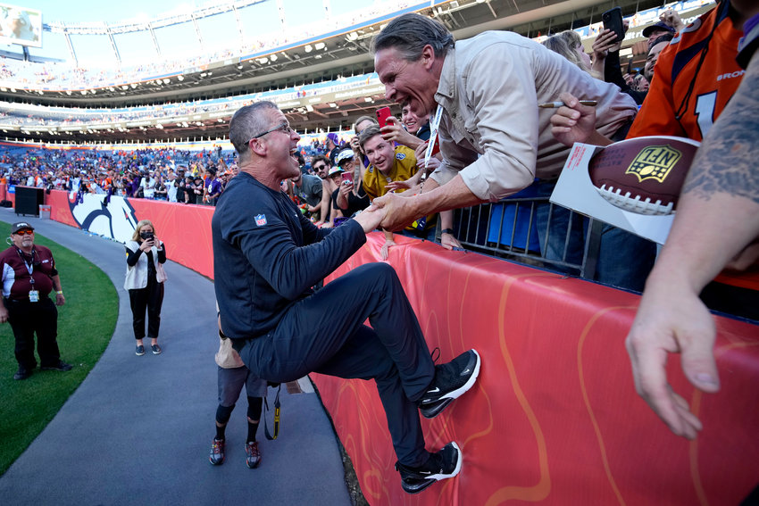Baltimore Ravens owner Steve Bisciotti pulls head coach John Harbaugh up the wall to celebrate after an NFL football game against the Denver Broncos, Sunday, Oct. 3, 2021, in Denver. The Ravens won 23-7. (AP Photo/David Zalubowski)..
