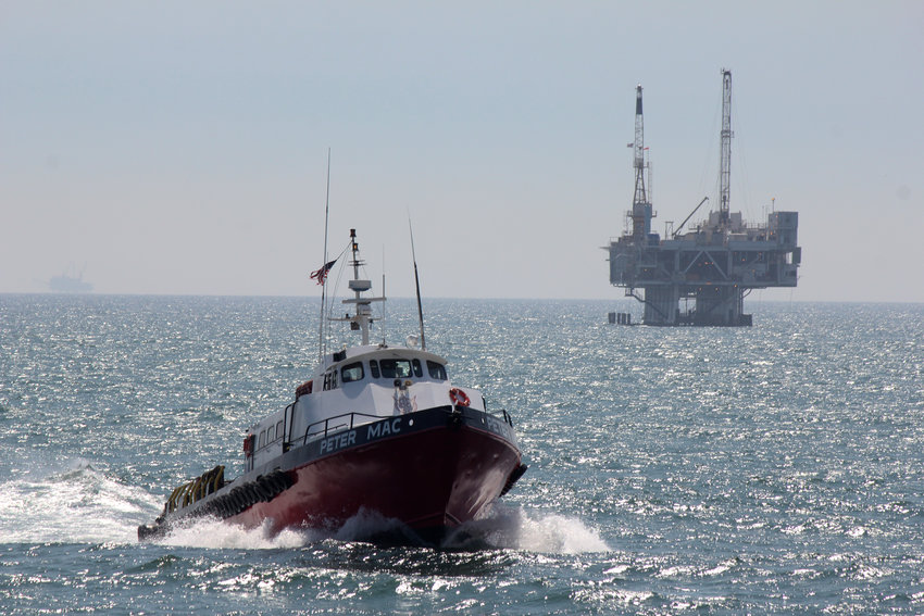 FILE- This May 16, 2015, photo shows a service boat carrying workers back to shore from a platform off Seal Beach, Calif. The recent oil spill off California's coast line has renewed calls to halt drilling off the state's coast.  California has been a leader in restricting offshore oil drilling but it has not been banned completely in state of federal waters. (AP Photo/John Antczak, File)