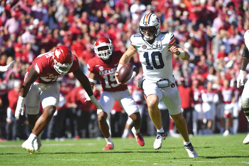 Auburn quarterback Bo Nix (10) slips past Arkansas defenders Eric Gregory (50) and Simeon Blair (15) as he runs for a touchdown during the second half of their game Saturday in Fayetteville, Ark.