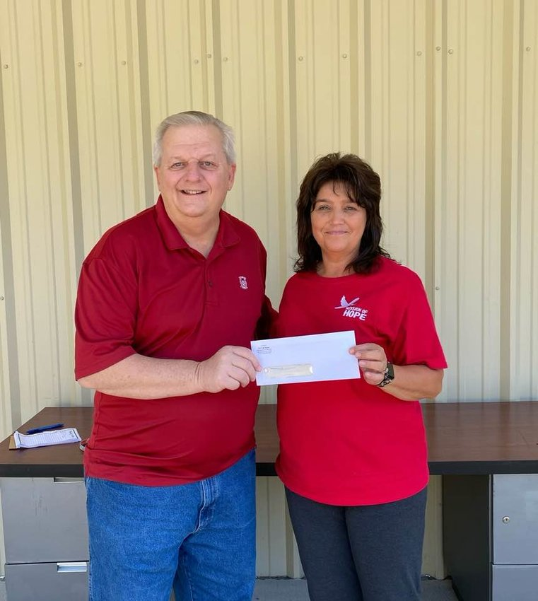 Dora Mayor Randy Stephens presents a $5,000 check to the Mission of Hope recently. The donation came out of the federal funds allotted to the city by the American Rescue Plan Act. Lori Campbell Abercrombie, director of the Mission of Hope accepts the check.