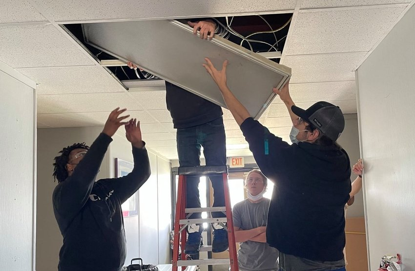 Walker County Center of Technology students work to replace outdated light fixtures with new LED lights at the school.