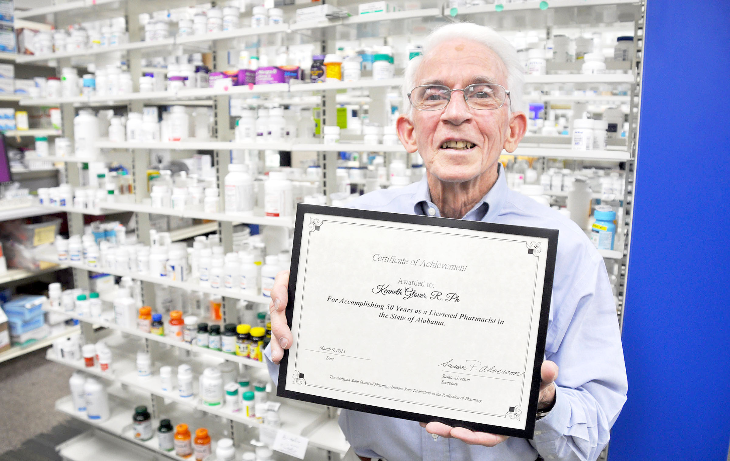 Sam Glover with his plaque of recognition for 50 years of practicing pharmacy. Daily Mountain Eagle - Dale Short