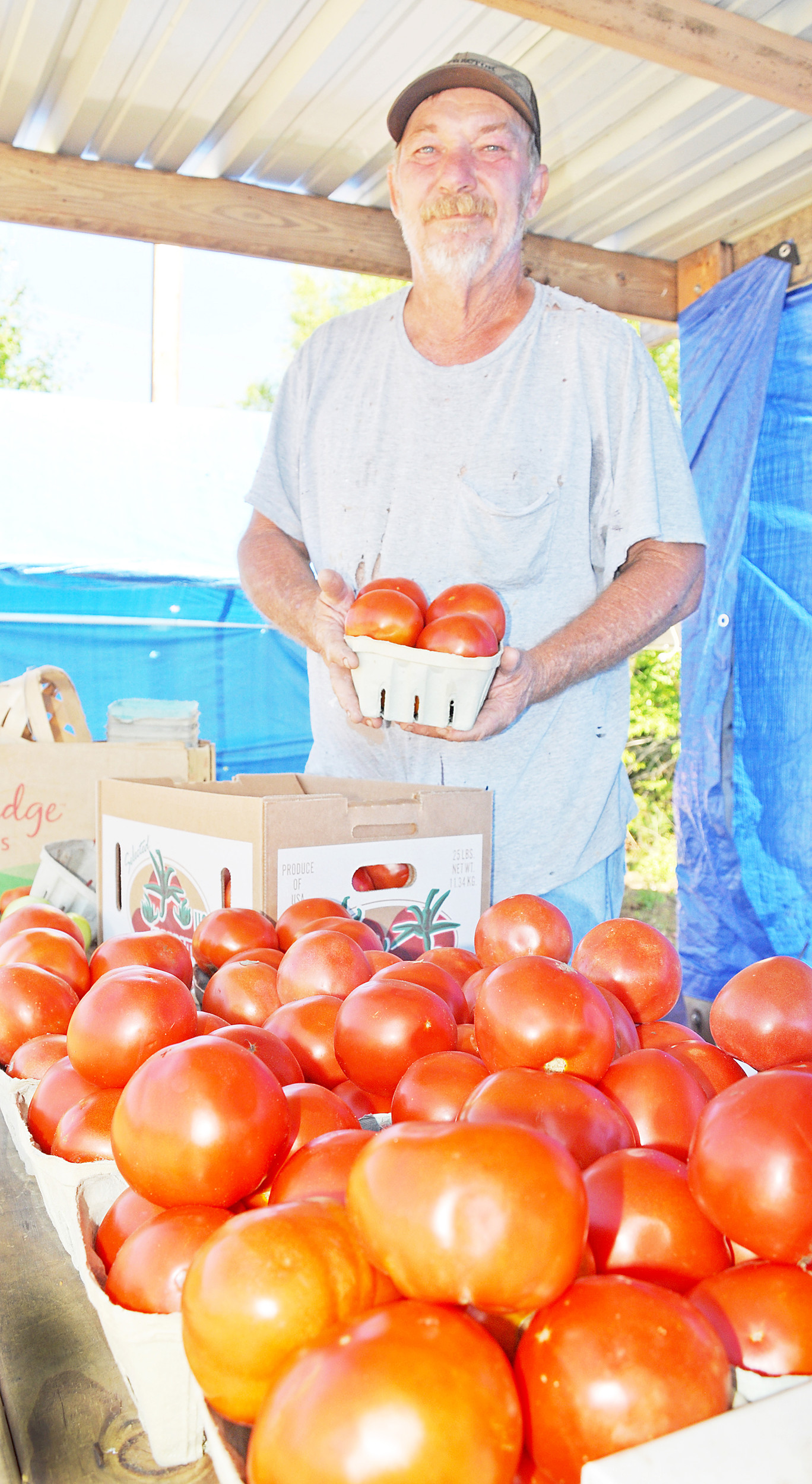 Tomato sales are highest on July 4 weekends, says vendor Johnny Bircheat. Daily Mountain Eagle - Dale Short