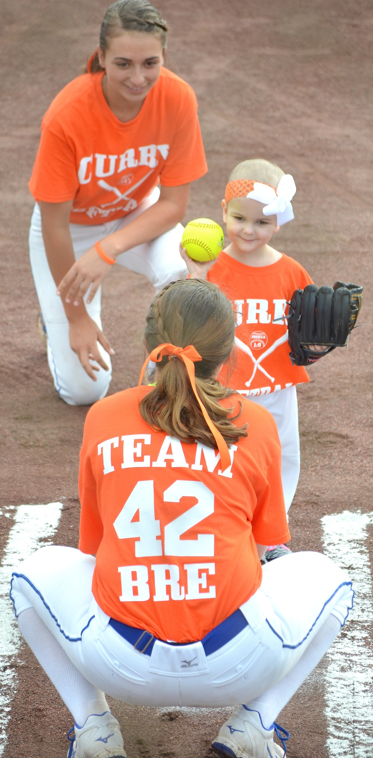 Brianna Cordell, 3, throws out the first pitch to her cousin Kylee Cordell as cousin Laycee Cordell looks on prior to Curry's home softball game against Dora on Monday. Brianna was diagnosed with acute lymphoblastic leukemia in September. Curry wore orange jerseys for Brianna on Monday. Orange is the color for leukemia awareness.