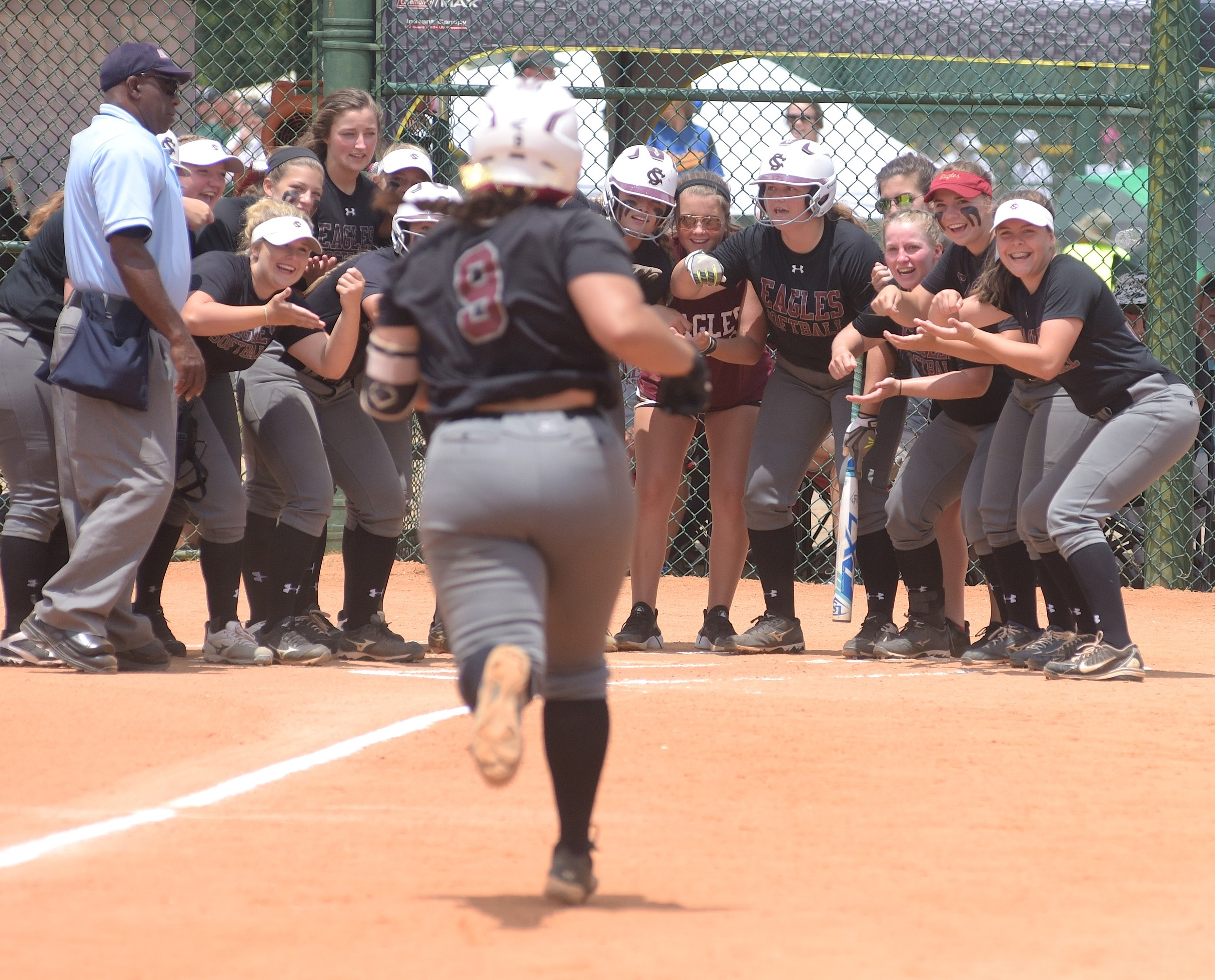 Sumiton Christian players await the arrival of Jenna Ergle (9) at home plate after the first of her two home runs against Marion County during their game at the State Softball Tournament in Montgomery on Thursday. Sumiton Christian won its state opener over Marion County (11-1) before falling to Pleasant Home (6-5). The Eagles play Ragland at 9 a.m. today.