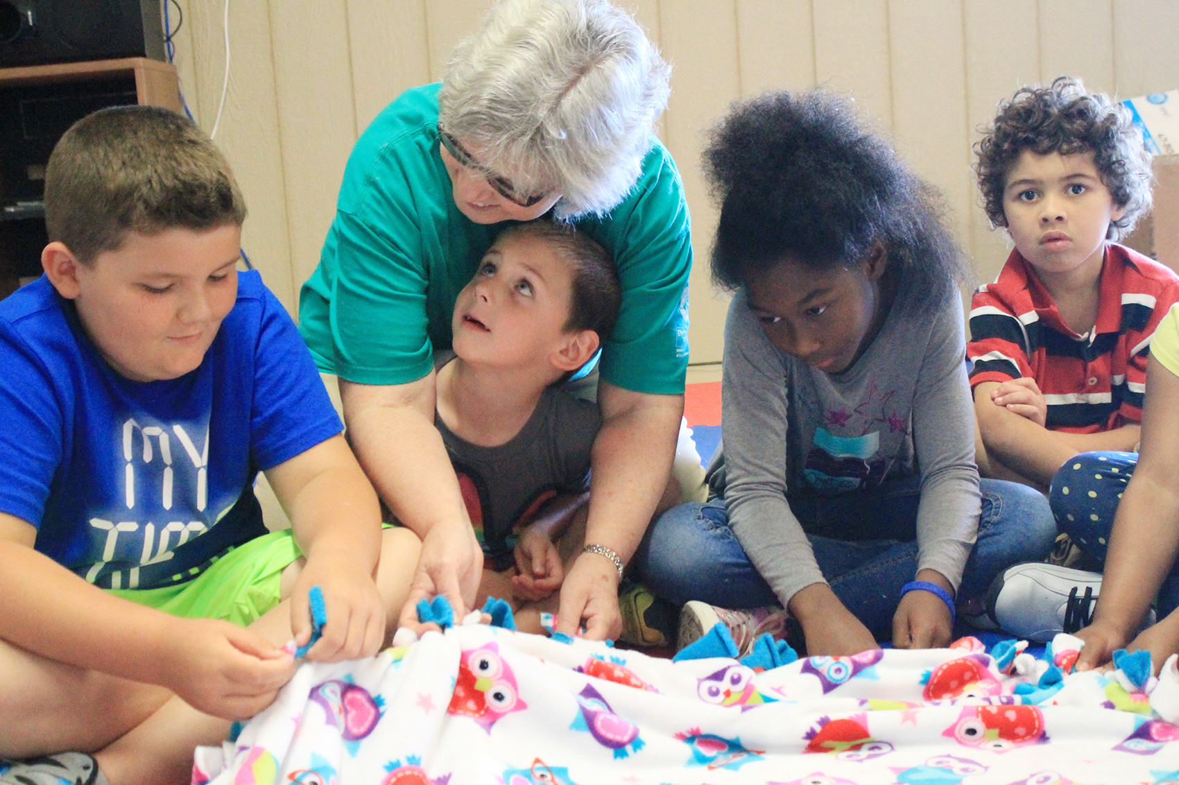 Jo Thomason, who is active with the local Retired Senior Volunteer Program, helps a group of children complete a no-sew blanket for area cancer patients during the Walker County Community Action Agency's summer program.   Daily Mountain Eagle - Jennifer Cohron