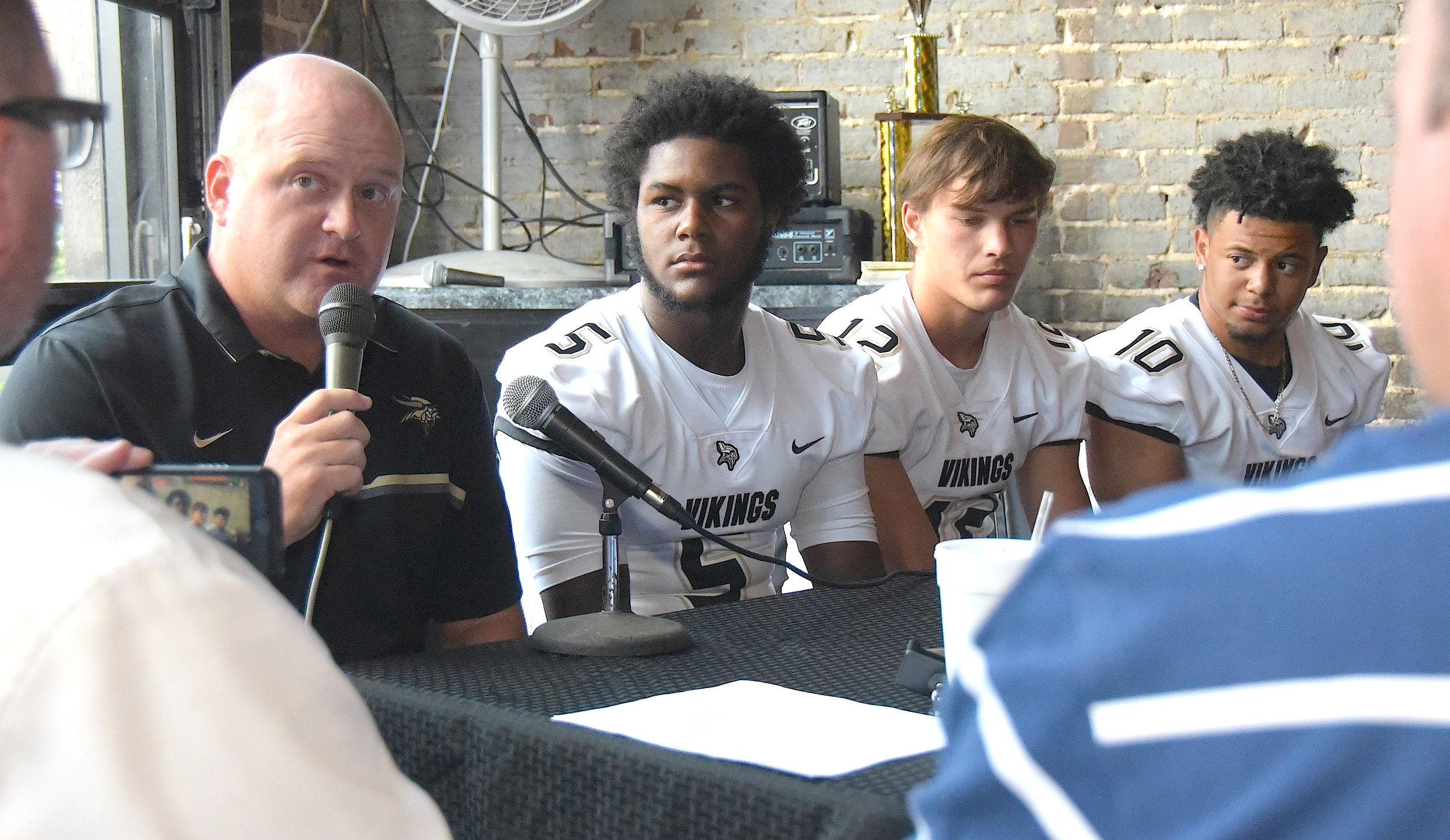 Jasper High School football coach Heath Brunner sits with players, from left, Jeremiah Hammond, Ethan Walker and Eli DeJesus during the first Walker County Football Media Day held at Warehouse 319 in Jasper on Monday. Coaches and players from Carbon Hill, Cordova, Curry, Dora, Oakman, Sumiton Christian and Jasper took part in the event.