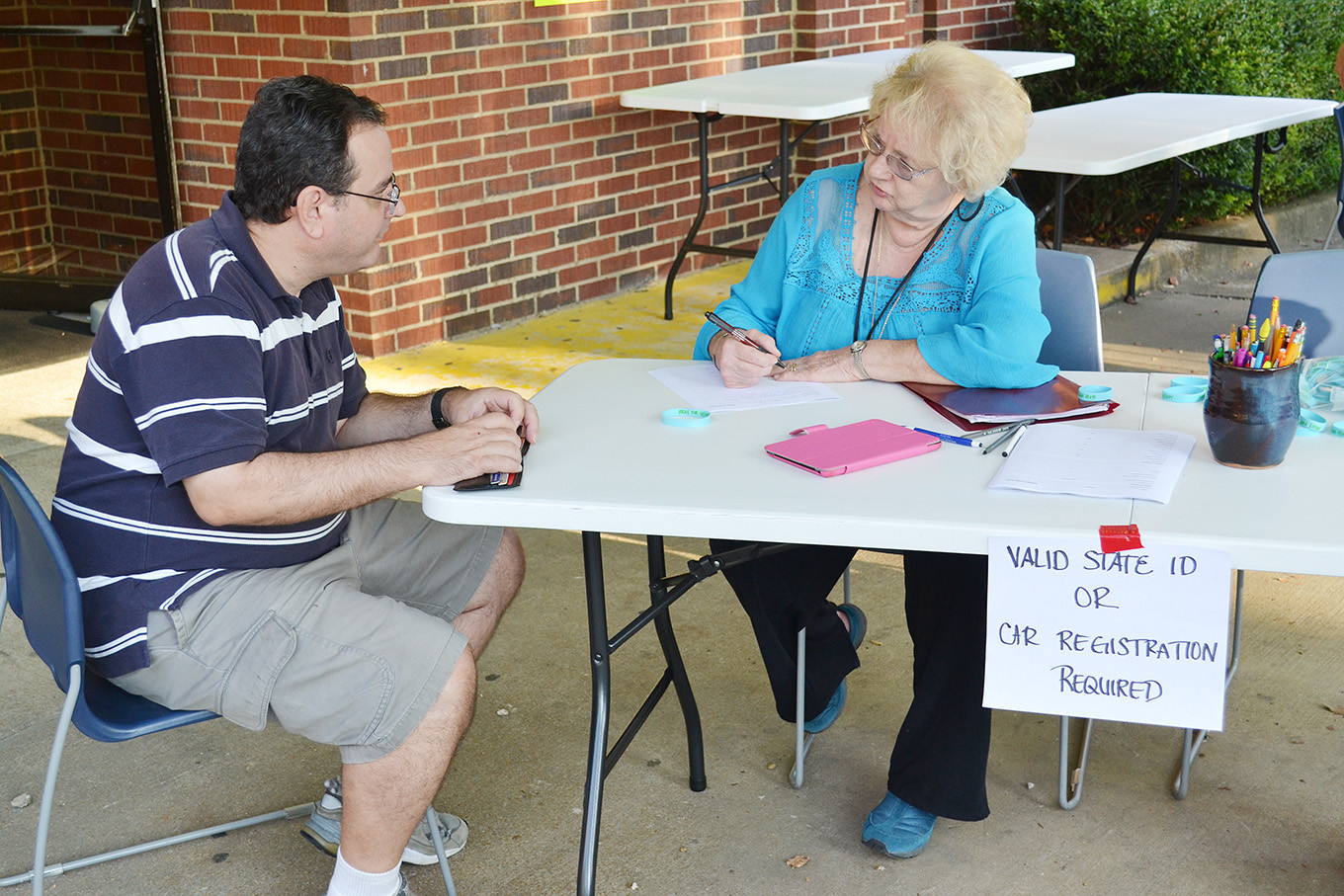 Stephen Caldwell, left, an evacuee from Naples, Fla., gives registration information Sunday night to Linda McCauley outside the shelter set up at First Baptist Church of Jasper.